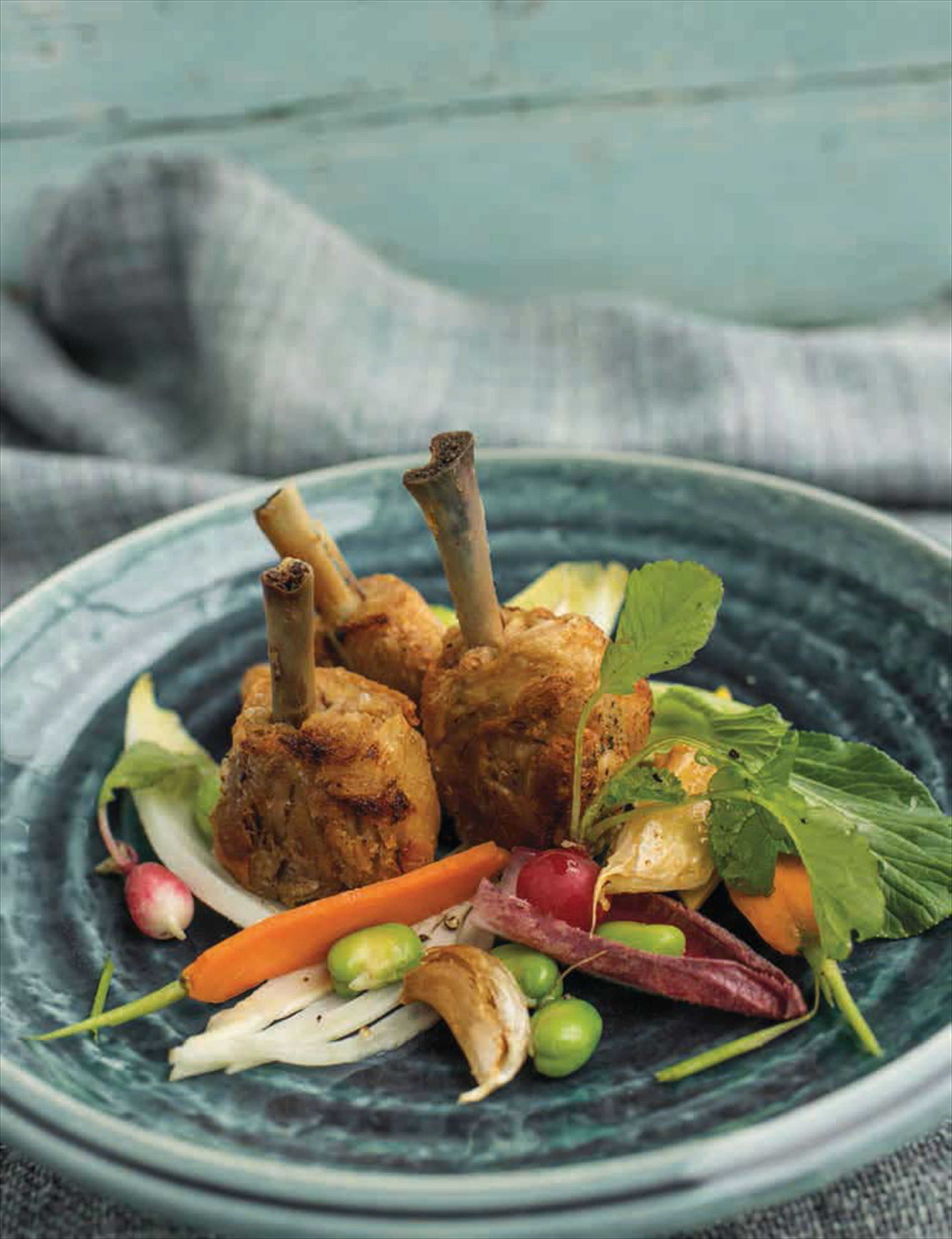 Chicken confit lollipops and garlic with raw vegetable salad