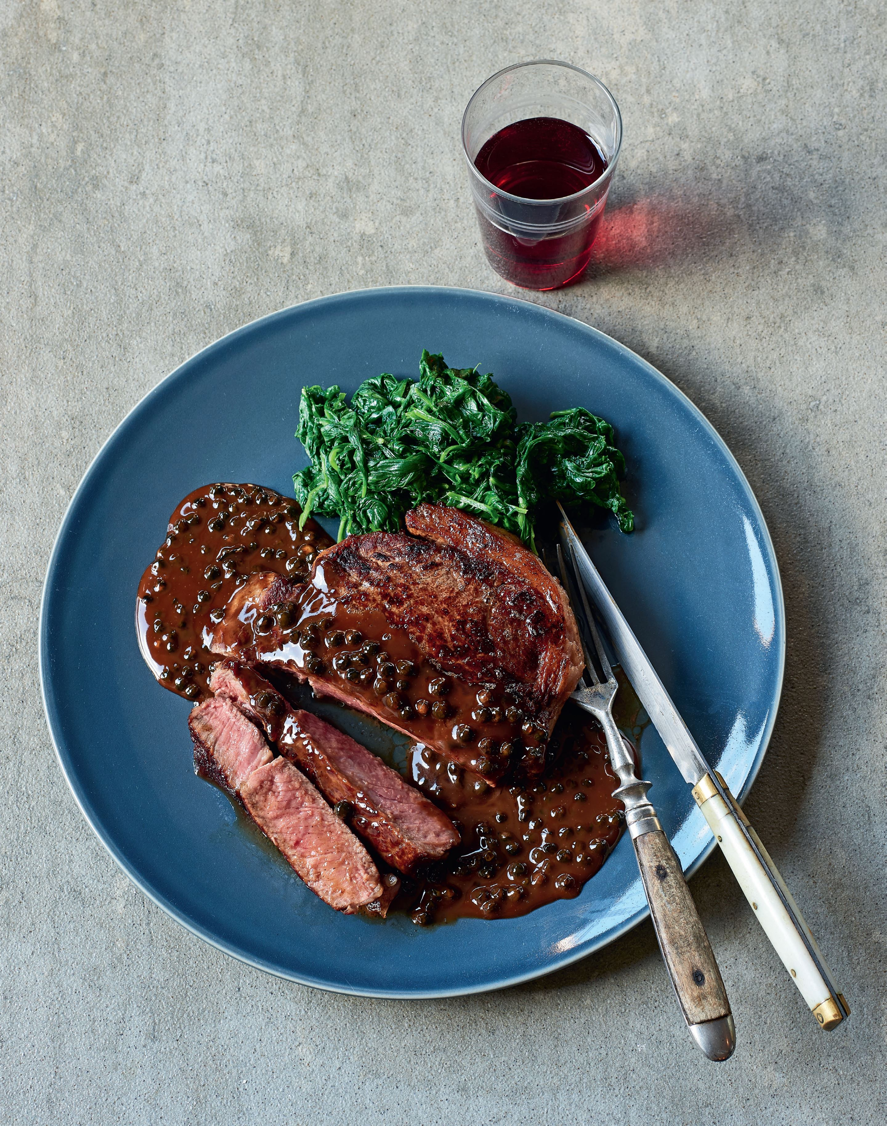 Steak au poivre with wilted spinach