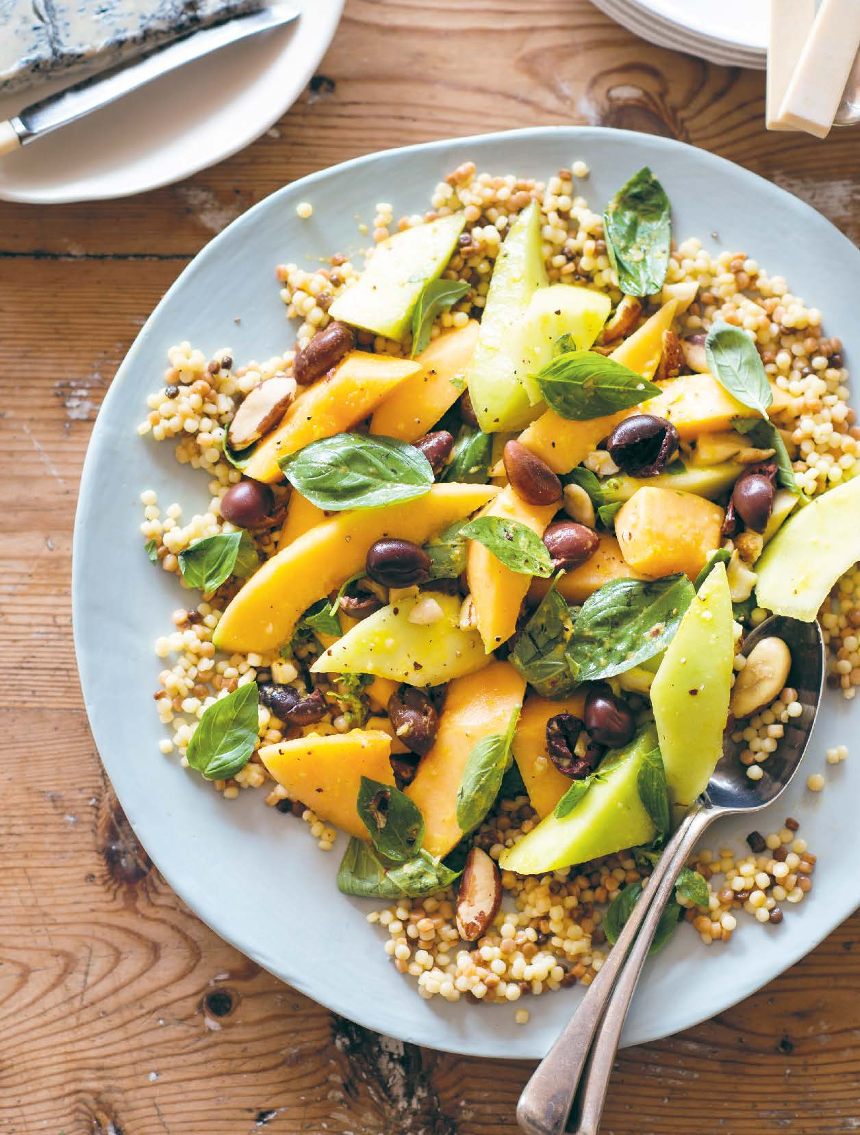 Melon salad with fregola, gorgonzola, olives and brazil nuts
